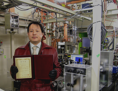 Dr. Hiromitsu Tomizawa in front of verification test equipment for the z-polarized photocathode electron guns he developed